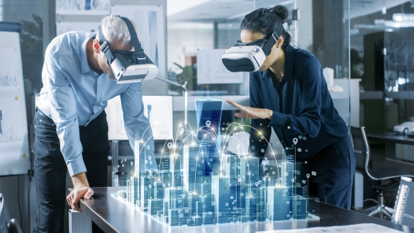 Male and Female Architects Wearing  Augmented Reality Headsets Work with 3D City Model. High Tech Office Professional People Use Virtual Reality Modeling Software Application.